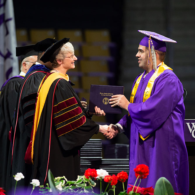 A student being given their degree from Interim Chancellor Dr. Alison Morrison-Shetlar